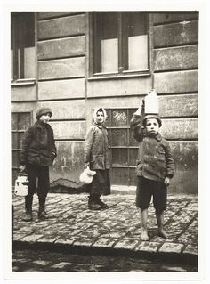 After the pogrom, children who have received food from a soup kitchen pose on a sidewalk with pitchers and soup pails. Lvov, 1918.