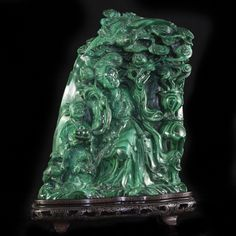 """DESCRIPTION:Hand Carved Chinese malachite sculpture. Features an illustration of an amiable regal woman and girl surrounded by ornate pillars and blooming trees garnished with flower bulbs. The young girl is seen holding a dish of fruit and the woman is seated grasping a vine with fruits. Finished with a highly ornate and detailed bird topping the piece and rests on a wooden stand decorated with traditional Chinese designs. CIRCA:Early 20th Ct. ORIGIN:China DIMENSIONS:H:11.5"""" L:9"""" W:4"""""""