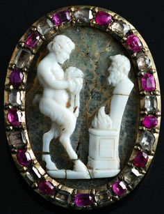 Renaissance cameo of Satyr and Pan. Italian. Two layers agate cameo engraved in low relief with the subject in opaque white chalcedony on the bkground of cracked translucent chalcedony.   The choice of the material, quality of the execution & correctness of the composition point to the 17th century. The French gold frame is alternately set by diamonds and by ruby cut in table, it seems to date end of the 17th C / beginnin 18th century.     mounting 32 x 26 mms.  cameo 27 x 19 mms