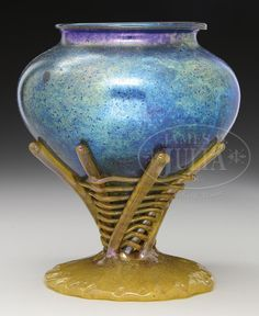 LOETZ DECORATED VASE. Loetz vase in Norma decor has bulbous body in blue iridescence with platinum highlights around body and rich purple highlights at neck. Vase is supported by applied amber glass foot with heavy glass fingers extending up side of vase with horizontal heavy threaded basket weave entwining with fingers. Vase is finished with applied amber glass lip. Unsigned.