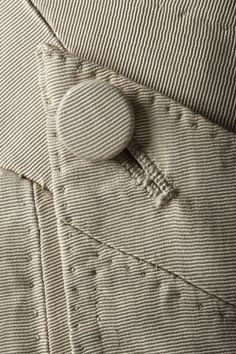 Detail of the fastening on a pair of breeches from a man's cream silk wedding suit, 18th century, part of the costume collection at Ham House, Surrey. National Trust Image # 194065
