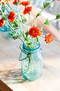 Orange flowers in blue mason jars