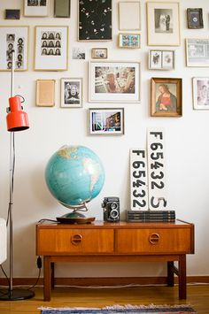 Antique globe, photos, camera, lighting and thrift bench.