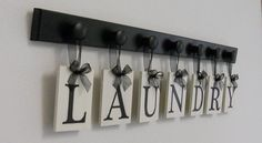 LAUNDRY letter sign hanging on wood knobs painted black or brown (select color). Select the number of tiles needed for your name or sign. Select 7 tiles for LAUNDRY (Choose more tiles if you would like to add the designs) Link to our design images: