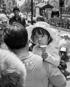 Cute child with an ice cream notices the man with a camera walking behind her in a busy high street Suzhou southeastern Jiangsu Province East China. I just happened to see her a few feet ahead of me. In this situation because I was walking and photographing and also my subject was also moving I went for a speed of 320 to freeze the action and a good depth of field F9 ISO 400. I also over exposed by about about one stop because the girls face was slightly shaded. #bnw_life #bw_lover #bw…