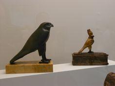 A gauche : Cercueil de rapace en alliage cuivreux 23X23,3X9,7cm – Basse Epoque.  A droite : Cercueil de rapace en bois de tamaris stuqué, doré et peint 23,5X23X8cm – Epoque ptolémaïque.