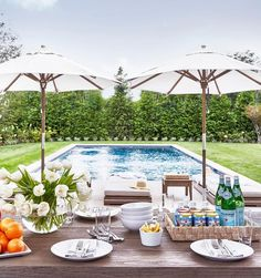 A taupe stained oak dining table shaded by two white umbrellas stand in front of an in-ground pool surrounded by lush green grass.