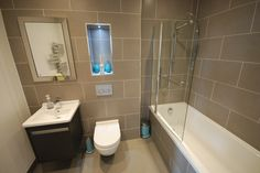 For this guest bathroom i choose a light grey tile and had it set in a modern brick style finish. The recess has LED lighting and the controls for the shower are at the entrance to the bath. The mirrored cabinet is also recessed into the wall to maximise space and storage. Turquoise is the accent colour for the accessories.