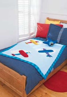 Bright airplanes fly across a blue sky in this fun and colorful blanket.
