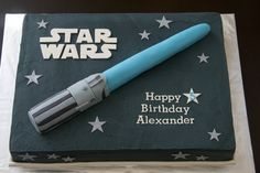 Star Wars chocolate cake with buttercream icing. Rice Krispie light saber covered in fondant.