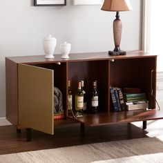 Striking yet unassuming, this Midcentury modern style console is the perfect organization piece for your home. Color blocked matte gold and walnut brown finishes add a contemporary touch to the smooth, retro styled body, which is free from visible hardware. Black tube legs uphold the console, completing the minimalist form. Featuring both touch-open and pull down cabinets, the storage options for your blankets, entertainment accessories or games are bountiful. The anywhere design makes this…