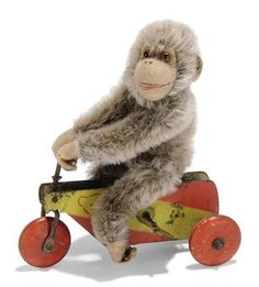 A STEIFF CLOCKWORK URFIPS, (9318), brown mohair chimpanzee, brown and black glass eyes, felt face, ears, hands and feet, swivel head, jointed and FF button with remains of white paper tag, seated on red and yellow steel tricycle, Teddy Bear head stencil and three wooden wheels, circa 1927 --7in. (18 cm.) high (faded and some wear to bike)