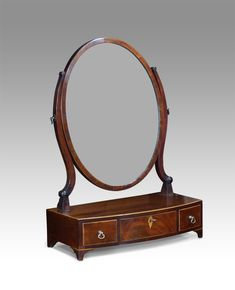 Dressing and Toilet Mirror - George III mahogany toilet mirror. Oval glass plate set within a crossbanded frame on shaped supports. Bowfront base, with three drawers with boxwood stringing and fitted with small brass handles. circa. 1790