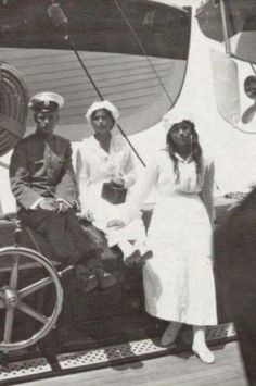 """Grand Duchesses Olga and Maria Nikolaevna Romanova of Russia with an officer on board the Imperial Royal yacht,the Standart. """"AL"""""""
