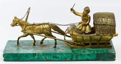 Lot 135: Russian Style Gilt Metal Horse and Sled; Having a cast metal statue of a Cossack style sleigh driver with horse mounted onto a Malachite style plaster and stone plinth; unmarked