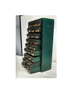 little green vintage 27-drawer cabinet for storing and organizing found objects and knick-knacks
