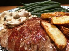 Steak with new potato chips, steamed green beans and creamy onion and mushrooms