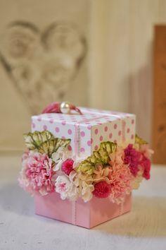 ピンクカーネーションやジャスミン、マムなどの小花を可愛い小箱に詰めた、とてもキュートなボックスアレンジメントです。 いつまでも可愛らしく元気でいてほしいお母さんへ贈る、可愛らしさあふれるアレンジメントです。