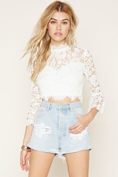 A semi-sheer woven eyelash lace crop top with 3/4 bell sleeves, a mock neckline, an exposed back zipper, and a scalloped hem.