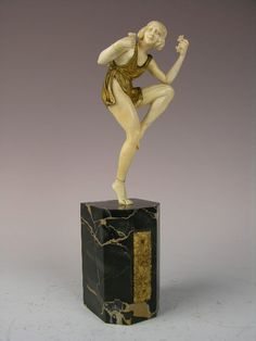"RLAUREL (FRENCH:WORKED 1920s) BRONZE AND IVORY DANCE CALLED ""ROSE DANCER"" THE DANCER HAS SEVERAL ROSES IN BOTHE HANDS AND CLAD IN A SHORT DRESS.SIGNED ""P. LAUREL"" IN THE BASE.MOUNTED ON A BLACK AND GOLD VEINED MARBLE BASE."