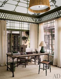 A Los Angeles home decorated with a painted trellis motif. The desk and upholstered chair are by Restoration Hardware.