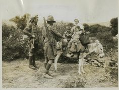 Photograph of ANZAC soldier and British soldier with Turkish woman, her children and donkey. The soldiers are giving them a drink of water. No 3127. From a collection of official photographs of the Dardanelles Expedition, 1915.