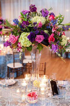Tall floral centerpiece arrangement for wedding reception.  Green hydrangeas, pink roses, blue & purple flowers.