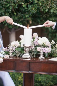 Bride & groom light unity candle during outdoor ceremony; floral arrangement sits on table during ceremony | Melissa Jill Photography | villasiena.cc