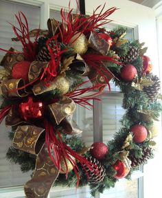 This wreath design was created on an 18 evergreen wreath base. It is elegant in red and gold for the holiday season. I used a beautiful ribbon, natural pine cones, red and gold ornament balls, and bright red feathers to complete this look.    Message me with questions