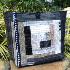 Hand quilted sashiko style patchwork tote bag in black and white and taupe. Made almost entirely from repurposed linen and linen-cotton clothing. A few pieces of vintage hand stitched table linens are part of the log cabin motif on the front of the bag. The back of the tote is a beautiful piece of wax resist African fabric. The lining is a reused mens dress shirt and there are three interior pockets. Simple loop and button closure. The tote measures 14 inches high by 17 inches wide and has a…