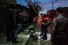 Investigators inspect the body of an alleged drug dealer as he lies in the gutter of a Manila street in early October