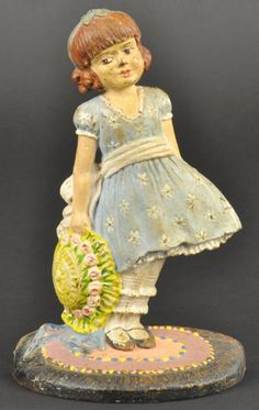 "GIRL WITH BONNET DOORSTOP ""Pat. Apl'd For Trade-Mark"" on back, Waverly Studios, CT, depicts inquisitive girl on braided rug holding sunbonnet, elegant pastel coloring, adorable piece. 8"" h. (Pristine Cond.)"