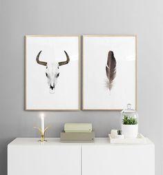Poster mit Büffelhörnern auf einem Sideboard.