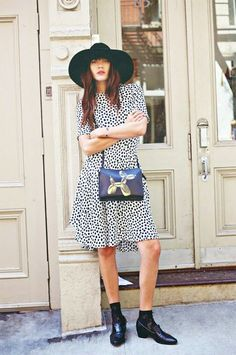 Natalie Suarez wears a polka dot dress, crossbody bag, loafers, lace socks, and a felt hat | Embour.com