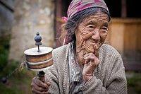 Une vielle femme Tamang priant et chantant des mantra avec son moulin à prières. Région du Langtang, Népal