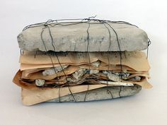 Ines Seidel -  'shape of a story',  book pages with plant parts, concrete, wire.