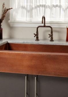 This farmhouse sink features a hammered apron and interior, giving it a distinctive appearance. Its lustrous copper patina will look beautiful in earthy and shabby chic kitchens.