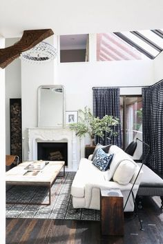 white sofa, cocktail table, flatweave rug, chandelier, floral, branches, checkered curtains, blue, living room, family room, white fireplace