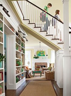 source: BHG  Cool passageway, under floating staircase, composed of beautifully styled built-in bookcases and brown sisal runner.