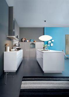 Integrante da linha Contino, esta cozinha, cujos armários receberam laminado de alto brilho, exala leveza e elegância incomum com a combinação de branco, azul e cinza. Sem puxadores aparentes, torna-se clean. A bancada tem 80 cm de altura para oferecer bom espaço de armazenamento, e um vão logo abaixo do tampo parece fazê-lo flutuar. Design da alemã Leicht.
