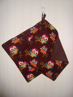 Set of 2 potholders with adorable, big-eyed owls on a brown background. Back is brown with white pin dots.