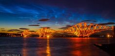 Noctilucent clouds, the highest in the the atmosphere at around 50 miles above the Earth's surface, captured here by photographer Adrian Maricic, from Fife, Scotland over the Forth Road and rail bridges.