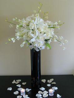 Decor Galore - All White Tall Cilinder Black Vase; White Hydrangeas, White Blizzard Roses, White Calla Lilies, White Oriental Lilies, and White Dendrobium Orchids