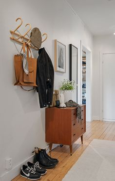 Hallway. Bright, simple coat rack, lovely midcentury dresser and wooden floors.