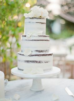 Three tier flower topped naked wedding cake: http://www.stylemepretty.com/2017/01/25/the-most-stunning-al-fresco-wedding-by-the-sea/ Photography: Jose Villa - http://josevilla.com/