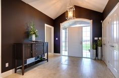 Design Ideas: Large Foyer With A Wooden Console Table In Black. spacious foyer. wooden chest. simple pendant light. dark foyer.