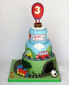Birthday Train Cake, 3 levels plus balloon topper (mountain and cods), 3-d engine at base, tunnel, fondant 2-d train cars. On fondant-covered cake board.