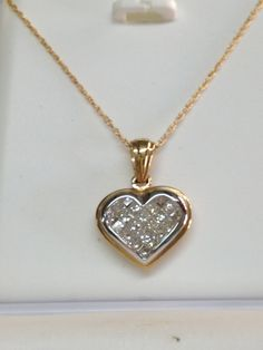14 Kt yellow gold with 9 princess cut invisible set diamond heart shaped necklace at The Golden Butterfly Jewelers.
