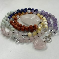 Malas, a string of 108 beads plus a head bead or 'guru' bead, are a traditional tool to use whilst meditating to help the mind focus and count mantras. Our chakra malas have been hand knotted by Georgie whilst listening to chakra and crystal meditation. These malas have 108 crystal beads and a Clear Quartz drop pendant as the guru. Each knot has been made with the intention of aligning the chakras. Crystal Jewelry, Crystal Beads, 2nd Chakra, Crystals Store, Rose Quartz Heart, Chakra Crystals, Wooden Beads, Clear Quartz, Plexus Products