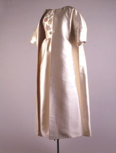 """Ivory Evening Coat Maker: Hubert de Givenchy (Fashion Designer, French, b. 1927) Date(s) of Materials: Spring-Summer 1961 Place Made: France Medium: Silk Ziberline Dimensions: 61"""" center back Description: A full length collarless ivory silk coat with three-quarter length sleeves (model 3378). This coat has minimal seams and a plain front. With this magnificent opera coat Givenchy paid homage to his mentor Balenciaga by manipulating a great sweep of fabric."""